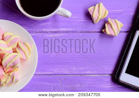 Little marshmallow on a plate, a cup of coffee, tablet on a wooden background with copy space for text. Female workplace in the office or at home. Top view
