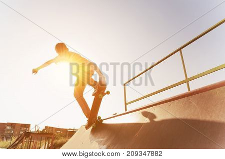 Teen skater hang up over a ramp on a skateboard in a skate park on sunset. Wide angle. Warm sunny picture