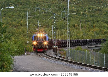 ABISKO, SWEDEN ON SEPTEMBER 03. View of an Electrical Ore Line Train in speed loaded with iron ore comes in on September 03, 2009 in Abisko, Sweden. Autumn, and lights on. Editorial use.