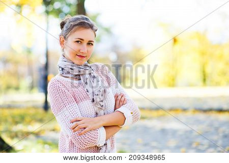 Young smiling teenage girl standing in autumn park