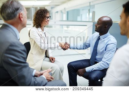 Successful business leaders greeting one another by handshake