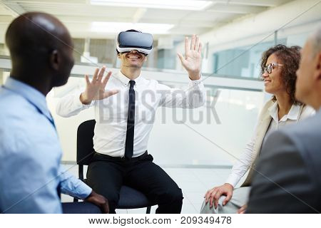 Happy businessman with vr goggles sitting among his colleagues looking at him