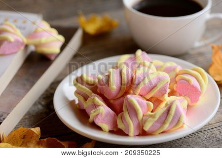 Pastel marshmallow on a plate, a cup of coffee, books on a wooden table. Macro. Autumnal breakfast or snack concept
