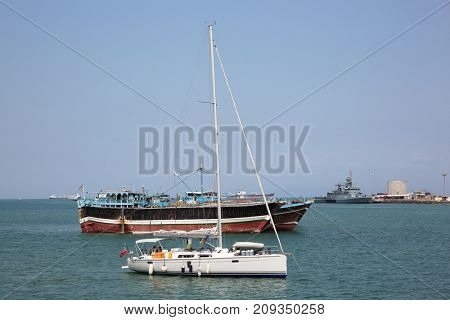GULF OF ADEN, DJIBOUTI: FEBRUARY 08, 2016: Luxury sailing boat, fishing and cargo ships at anchor in the port of Djibouti