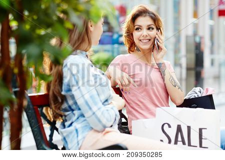 Friendly girls after shopping having rest on banch in the mall, one of them speaking on smartphone