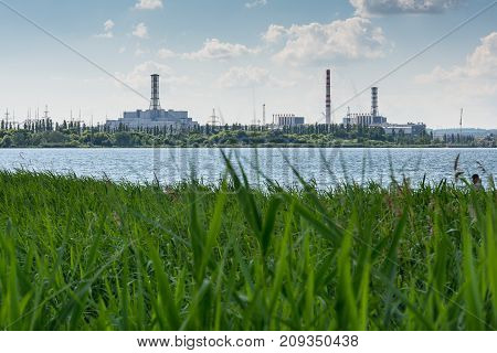 nuclear power plant on the shore of a lake with green grass