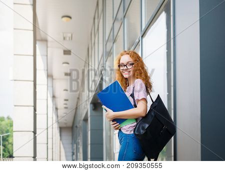 Happy redhead student girl with books, notepad and backpack. Attractive smiling young woman outdoors at college campus. Education, studying and entering the university concept