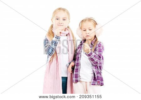 Portrait of two little sisters wearing scarf and earmuffs posing against white background