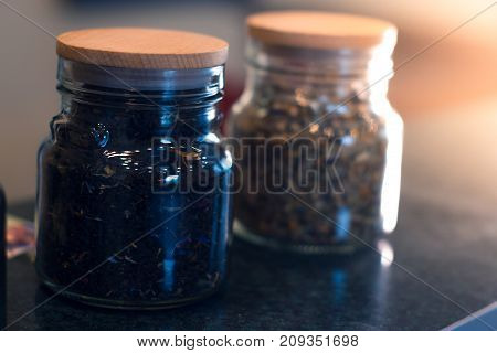 Different types of tea in glass jars on a blurred background