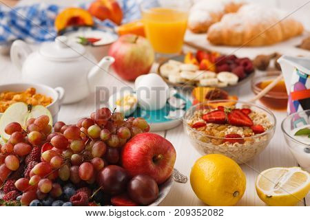 Fresh healthy breakfast with fruits closeup. Bowl with grapes, berries and apple with breakfast assortment on wooden table