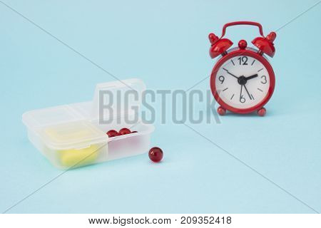 Red alarm clock pharmaceutical pills tablets and yellow capsules spilling out of daily pill box. Medical concept photo pharmacy theme