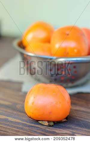 Fresh persimmon on wooden table and persimmons on collander