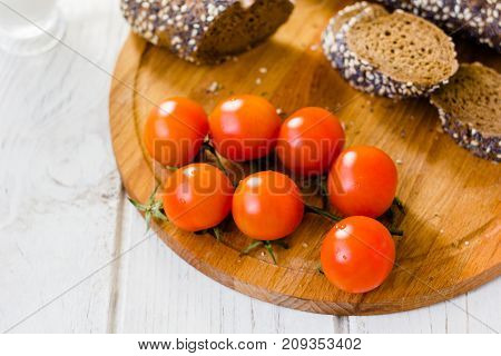 Bunch of cherry tomatoes over wooden board
