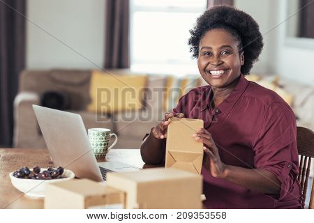 Smiling young African woman sitting at a table at home using a laptop and writing addresses on packages for her home based online business