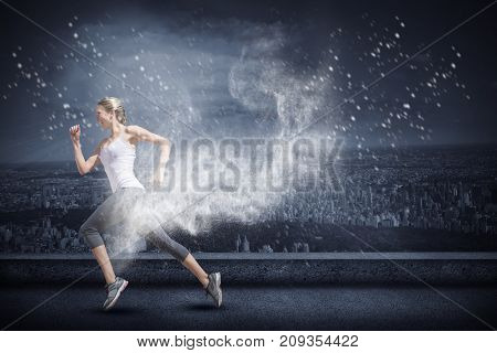 Pretty fit blonde jogging  against white dust powder