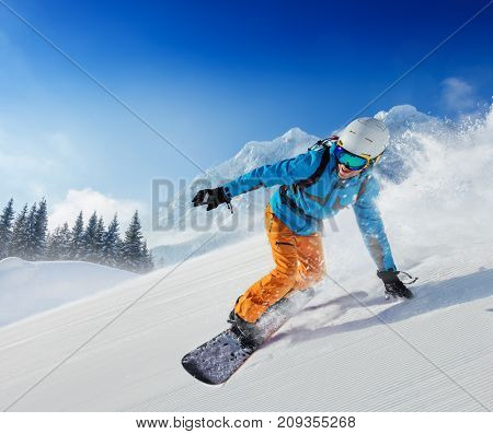 Young man snowboarder running down the slope in Alpine mountains. Winter sport and recreation, leisure outdoor activities.