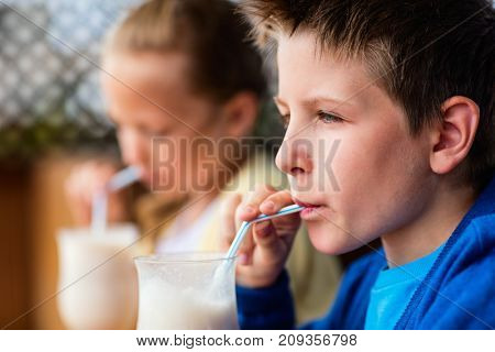 Kids brother and sister drinking milkshakes in outdoor cafe