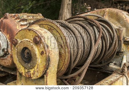 Old weathered used grunge iron reel with rolled steel wire and rusty electric motor to propel winch closeup