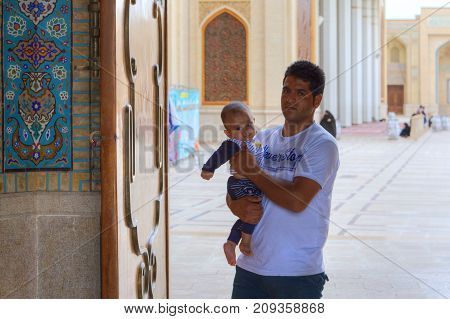 Fars Province Shiraz Iran - 19 april 2017: Shah Cheragh Shrine Muslim man with a small child in her arms pass through the large gate of mosque.