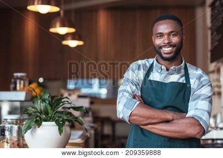 Portrait of a handsome young African entrepreneur smiling and standing welcomingly in his trendy cafe