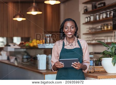 Portrait of a smiling young African female entrepreneur in an apron using a digital tablet while standing in her trendy cafe
