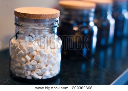 Marshmallow in a glass jar on a blurry background