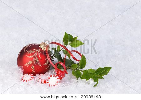 Christmas ornament with holly, ribbon and peppermint candy on snow