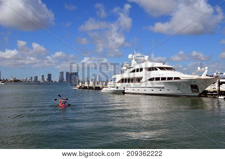 A couple in a rental kayak gliding by a luxurious white motor yachts moored at a marina on Miami Beach and in the distance Miami tall building skyline.