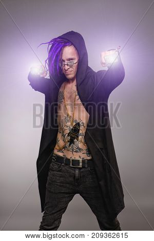 Cool punk rock musician in black clothes and with bright dreadlocks. Studio shot.
