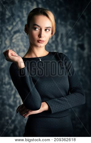Elegant blonde young woman wearing black fitting dress. Beauty, fashion concept. Studio shot.