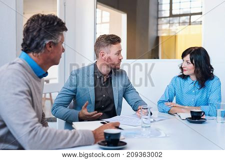 Focused young businessman talking with two work colleagues while sitting together at a table in a meeting room in a modern office