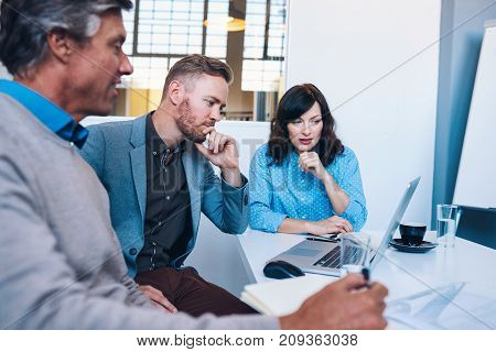 Three work colleagues talking and using a laptop together while sitting at a table in a meeting room in a modern office