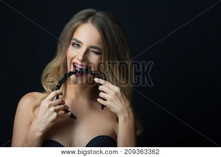 portrait of a beautiful young girl with makeup and hairdress on head on a black background biting decoration