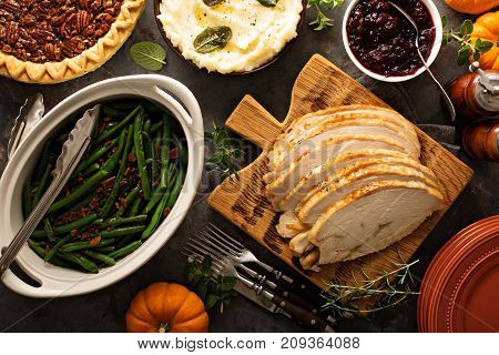 Sliced roasted tukey breast for Thanksgiving or Christmas dinner with side dishes overhead shot