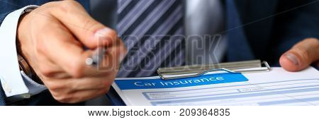 Male arm in suit offer insurance form clipped to pad and silver pen to sign closeup. Strike a bargain, driver money loss prevention, secure road trip, harmless drive idea, owner protective offer