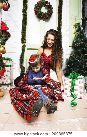 happy smiling family on Christmas at house with gifts, young mother and little son in Santas red hat, lifestyle holiday people concept close up