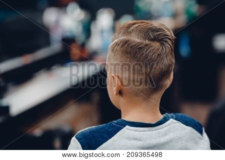 Barbershop. close-up example of children's fashion haircut, rear view in barber shop