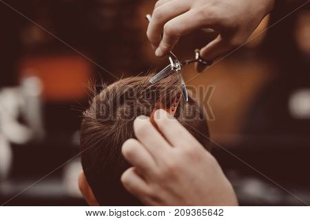 Barbershop. Close-up of man haircut, master does the hair styling in barber shop
