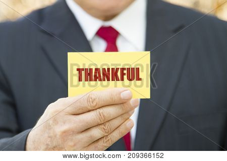 Businessman showing a card with text THANKFUL.