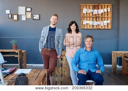 Portrait of three casually dressed work colleagues smiling confidently together while working in a large modern office