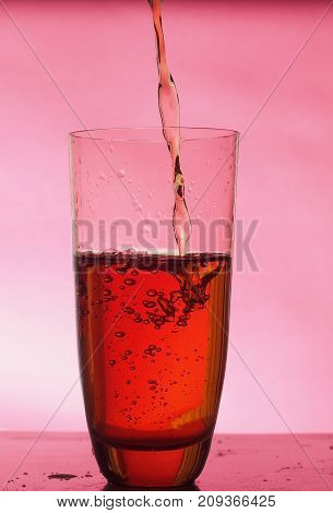 In a clear glass filled with drink. The on Burgundy background. Still life.