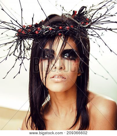 pretty brunette woman with make up like demon at halloween, closeup scary background