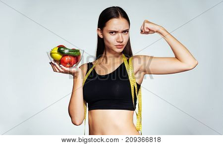 sports girl holding a plate of vegetables in her hands and showing all her strength, healthy life