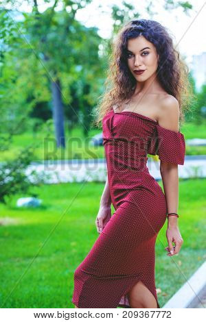 Charming woman dressed in elegant burgundy dress in a summer park. Beauty, fashion concept.