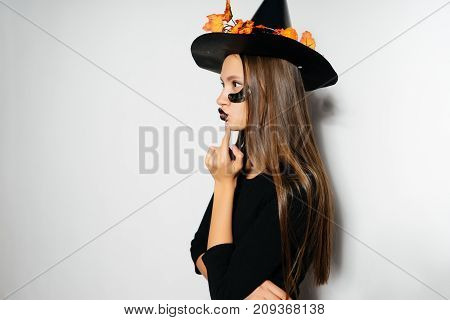 a fashionable Halloween witch in a big black hat with leaves gathered for a party, autumn celebration Halloween