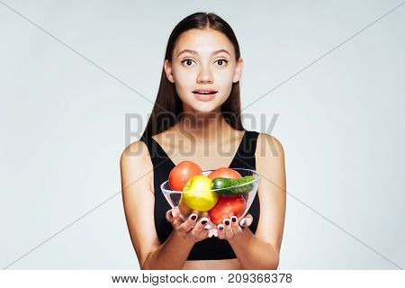 cute girl about to cook a vegetable salad and looks directly at the camera, isolated, healthy food, healthy life
