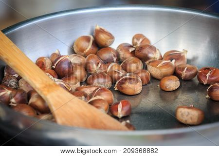 Warm fried edible chestnuts (castanea sativa) lie in a frying pan