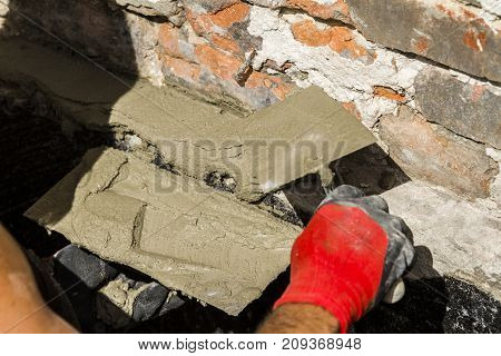 Worker with wall plastering tools renovating house. Plasterer renovating outdoor foundation and walls.
