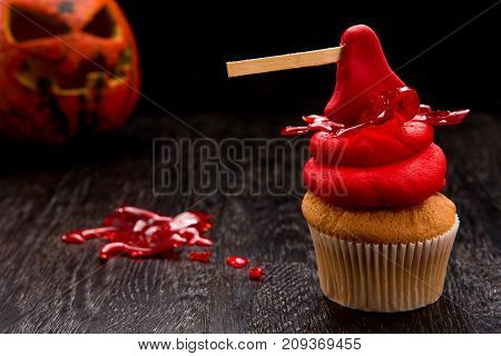 Halloween red one cupcake with ax. Cupcake with blood and monster pumpkin. Halloween decorated cookie on dark wooden table. Close up