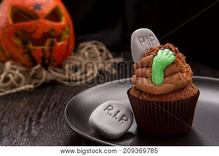Halloween cupcake with tombstone. Cupcake with pumpkin. Halloween cake on dark wooden table. Close up